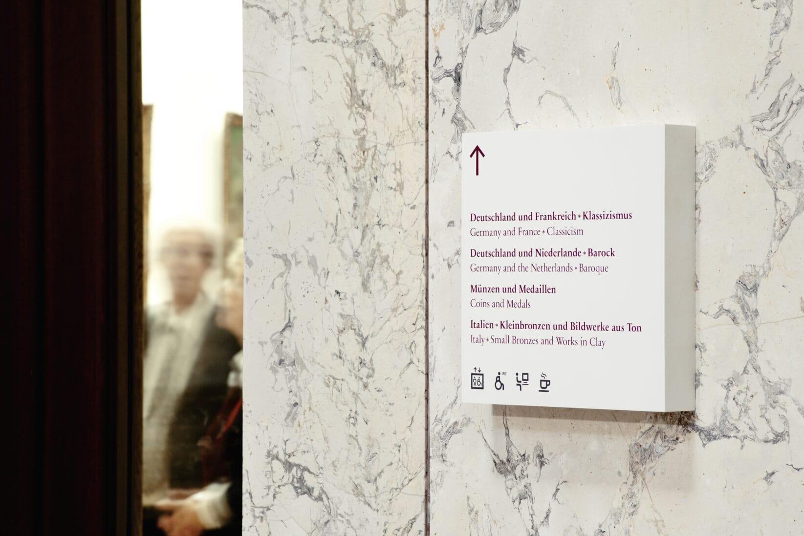 Museumsinsel Berlin Leitsystem Signaletik Gesamtkonzept Innenraum Wegweiser auf Marmor Besucherinnen