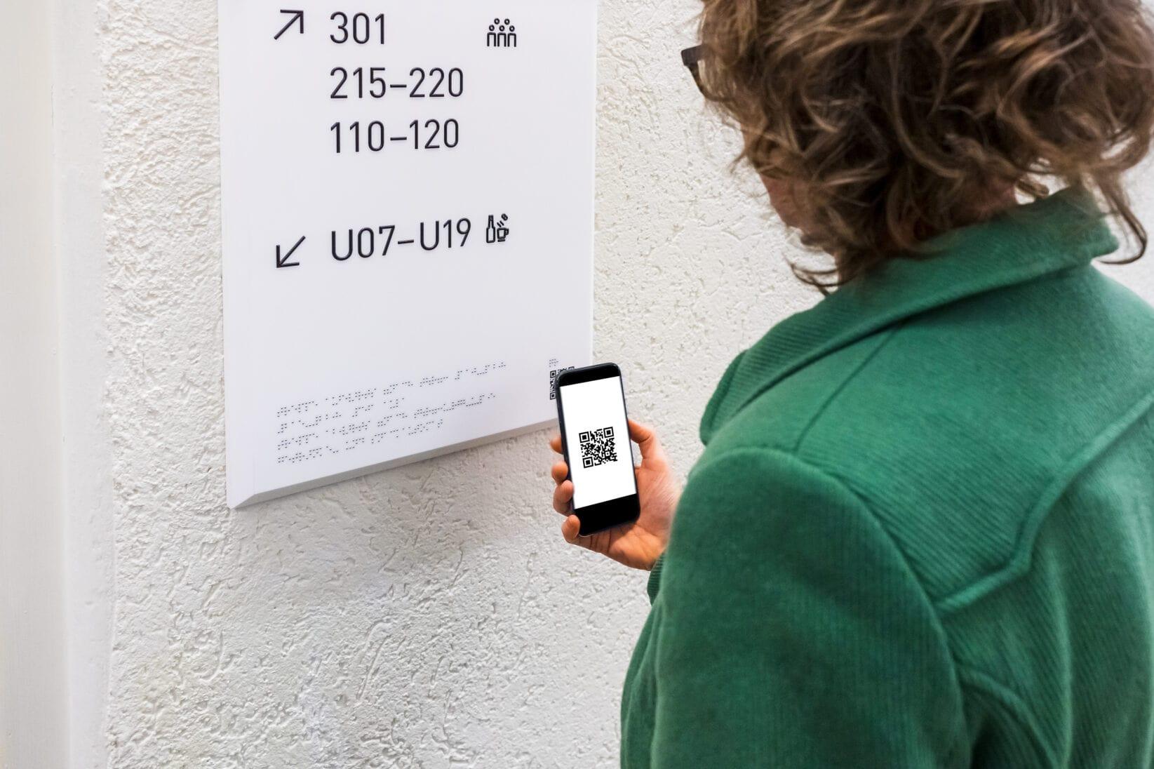 Alle Leitschilder der Volkshochschule sind mit einem QR Code ausgestattet. Hiermit können sehbeeinträchtigte Besucher*innen auf das akustische Leitsystem zurückgreifen.